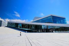Cheerful little boy runs in front of the Oslo opera building during a sunny summer morning, Oslo, Norway stock images