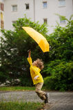 Cheerful little boy runs on the yard of the house with an umbrella in a hand. Royalty Free Stock Image