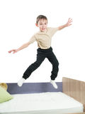 Cheerful little boy in a shirt and trousers jumping on the bed and waves his hands. On a white background Royalty Free Stock Images