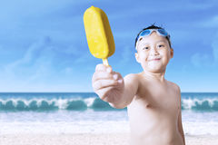Cheerful little boy showing ice cream Stock Images