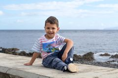 Little boy sitting on the beach. Cheerful little boy sitting on the seashore Royalty Free Stock Images