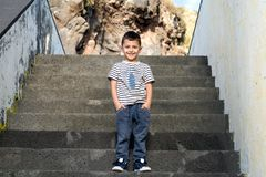 Cheerful little boy on the steps. Cheerful little boy is standing on the steps Royalty Free Stock Photography