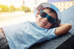 Cheerful little boy in sunglasses and hat resting on street stai Stock Images