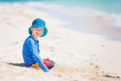 Kid at vacation. Cheerful little boy in sunhat and rashguard playing in the sand at tropical beach, sun protection concept Stock Photography