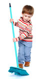 Cheerful little boy sweeping the floor with a Royalty Free Stock Photos