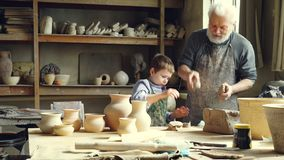 Cheerful little boy is throwing pieces of clay on work table while helping his grandfather in potter`s workshop. Happy stock video footage