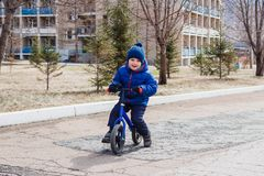 Cheerful little boy in warm clothes riding a children`s running bike in early spring. Outdoors royalty free stock images