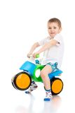 Cheerful little boy in a white shirt er. Cheerful little boy in a white shirt and blue shorts riding a two-wheeled plastic bike , he is a biker-Isolated on white Stock Photography