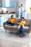 Cheerful little boys sitting on sofa and playing video games. Enthusiastic gamers. Pleasant little boys sitting on the sofa and playing video games, the little Stock Images