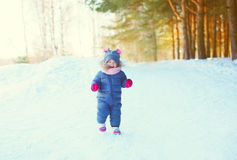 Cheerful little child playing on snow in winter Royalty Free Stock Images