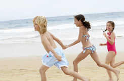 Cheerful Little Friends Running Together On Beach Stock Photo