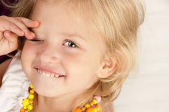 Cheerful little girl. Closing one eye close-up Stock Image