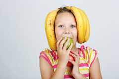 Cheerful little girl with apples, lemon and banana poses positively in studio royalty free stock photography