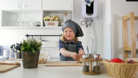 Cheerful little girl in apron rolls out the dough in the kitchen. Close up stock footage