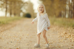 Cheerful little girl at autumn road Royalty Free Stock Images