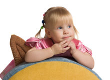 Cheerful little girl on a back of a armchair. Royalty Free Stock Photo