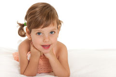 Cheerful little girl on the bedspread. A cheerful little girl is lying on the bedspread; isolated on the white background royalty free stock photography