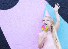 Girl with lollipop. Cheerful little girl with birthday cap on head holding lollipop royalty free stock image
