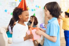 Cheerful little girl in birthday hat waits for her to receive gift box. Gift time. stock images