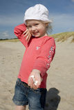 Cheerful little girl with cockle-shell Royalty Free Stock Image