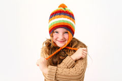 Cheerful little girl in colorful sweater and hat isolated Royalty Free Stock Photo