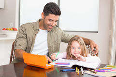 Cheerful little girl colouring at the table with her father Royalty Free Stock Photography