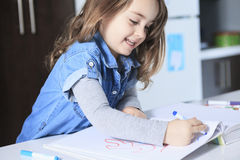 Cheerful little girl colouring at the table at Stock Photo