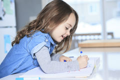 Cheerful little girl colouring at the table at Royalty Free Stock Images