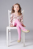 Sweet little girl sitting on the white chair, looking away. Cheerful little girl with curly long hair sitting on the white chair wearing pink clothes, making Stock Image