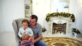 Cheerful Little Girl And Dad Having Fun And Fool Around, Laugh and Smile in Large Bright Room in Background Festively. Cute Blond Baby With His Father Reading stock video