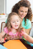 Cheerful little girl doing arts and crafts with mother at the table Stock Image