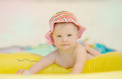 Cheerful little girl with Downs Syndrome playing in the pool. Cheerful little baby girl with Downs Syndrome playing in the pool Royalty Free Stock Images