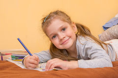Cheerful little girl draws lying on his stomach with a pencil Stock Photos