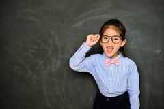 Cheerful little girl dress up school teacher. Cheerful pretty little girl dress up school teacher standing in blackboard background and feeling funny face to Stock Photography
