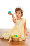 Cheerful little girl with Easter basket. A cheerful little girl is sitting on the floor near the Easter basket and holding an egg Stock Photo