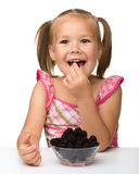 Cheerful little girl is eating blackberry royalty free stock photography