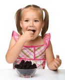 Cheerful little girl is eating blackberry Royalty Free Stock Photos