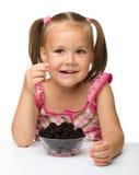 Cheerful little girl is eating blackberry Stock Photo
