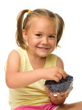 Cheerful little girl is eating blueberry stock image