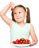 Cheerful little girl is eating strawberries Stock Photo