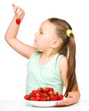 Cheerful little girl is eating strawberries Royalty Free Stock Photo