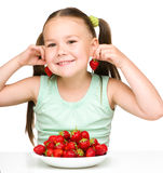 Cheerful little girl is eating strawberries Royalty Free Stock Photos