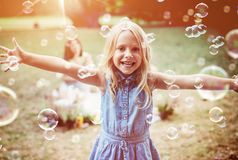 Cheerful little girl enjoying bubble blowing stock images