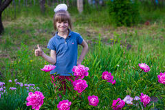 Cheerful little girl in flowers with thumb up royalty free stock image