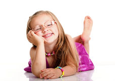 Cheerful little girl glasses funny is lying royalty free stock images