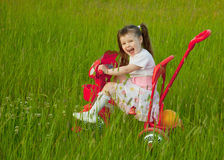 Cheerful little girl goes on a bicycle Stock Image