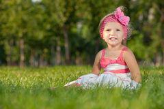 Cheerful little girl on the grass in the park Stock Photos