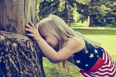 Cheerful little girl hiding behind tree Stock Photo