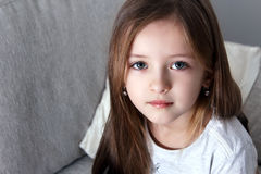 Cheerful little girl holding arms crossed and looking at camera Royalty Free Stock Images