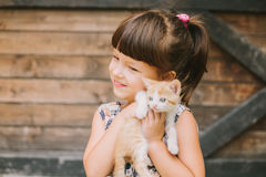 Cheerful little girl holding a cat in her arms Stock Images